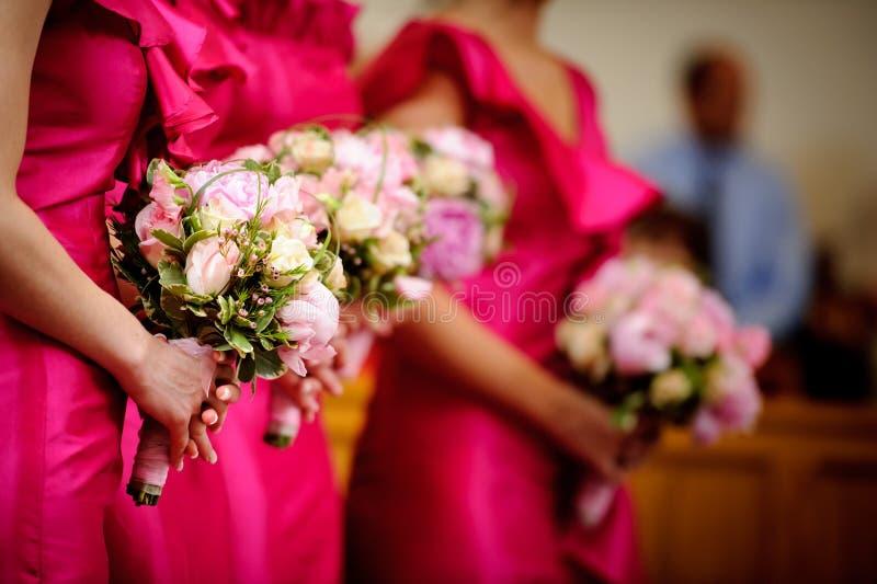 Rij van bruidsmeisjes met boeketten bij huwelijksceremo stock afbeeldingen