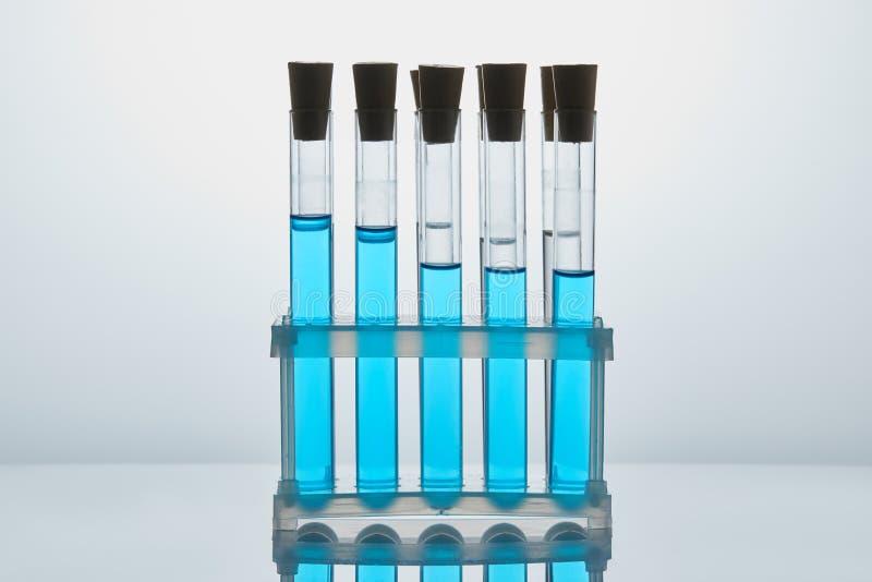 Rij van chemiebuizen met blauwe vloeistof worden gevuld die stock afbeelding