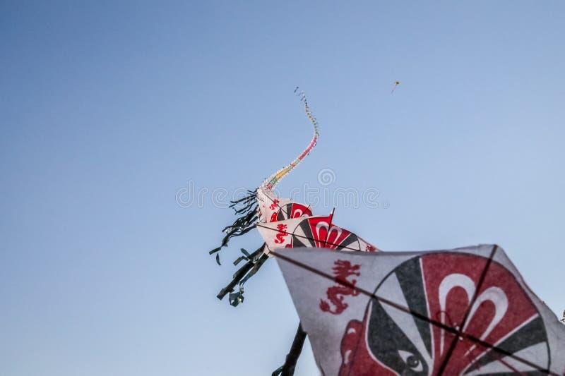 Rij van Chinese document vliegers die op duidelijke blauwe hemel vliegen royalty-vrije stock foto's