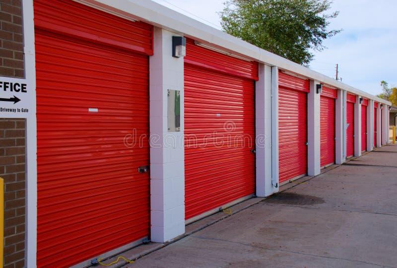 Rij van de eenheden van de opslaggarage met rode deuren stock afbeeldingen