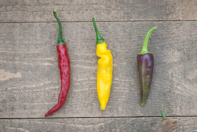 Rij van Drie Spaanse peperspeper op een Houten Lijst royalty-vrije stock fotografie