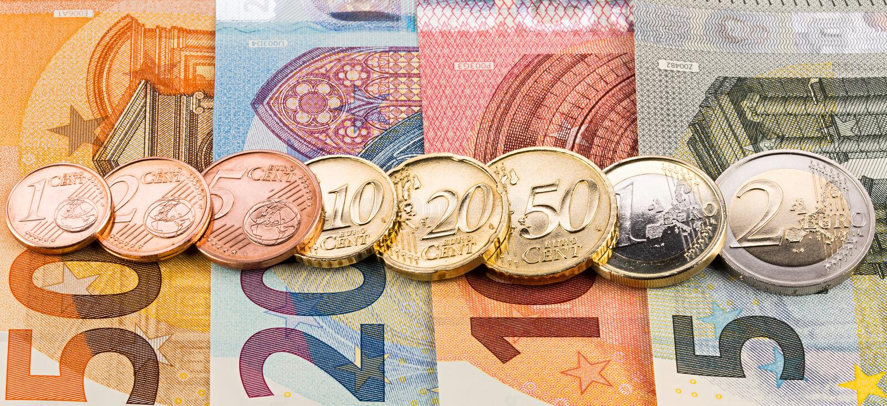 Rij van eurocentmuntstukken op bankbiljetten stock afbeeldingen