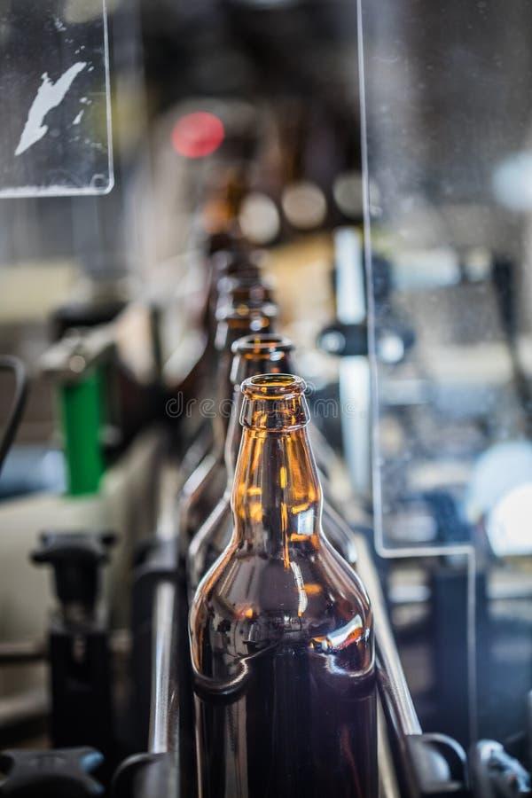 Rij van flessen op transportband stock afbeeldingen
