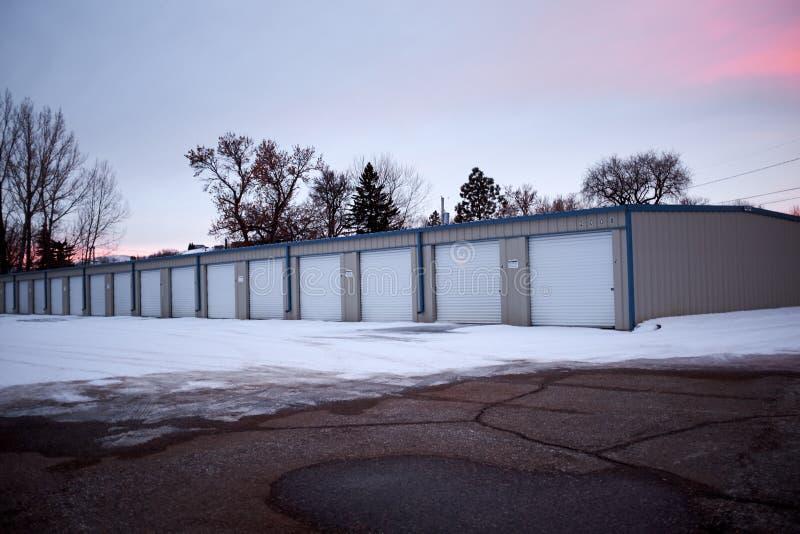 Rij van garages in de wintersneeuw bij zonsondergang stock foto's