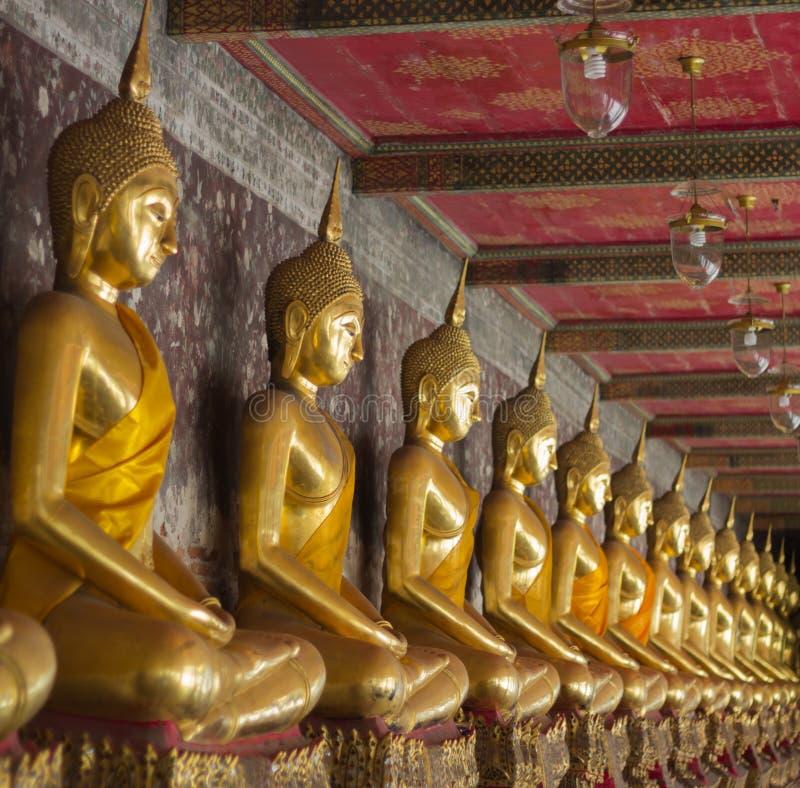 Rij van gouden gezette buddhas in een Boeddhistische tempel stock afbeeldingen