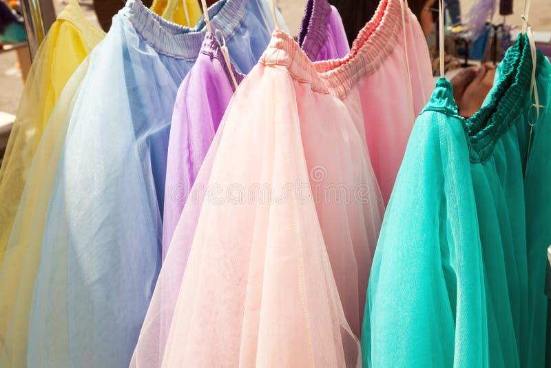 Rij van het hangen van kleurrijke gaasrokken bij een kledingsopslag stock fotografie