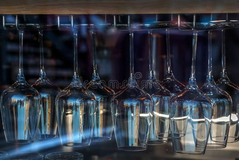 Rij van het schone wijnglas hangen op tribunebovenkant - neer in winkelvenster Veel wijnglazen drogen op droger stock foto
