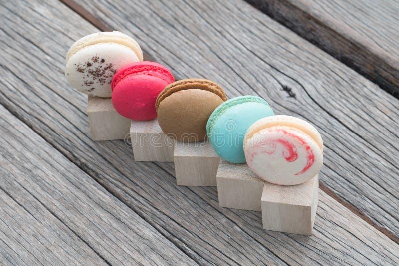 Rij van kleurrijke makarons op houten blok stock afbeeldingen