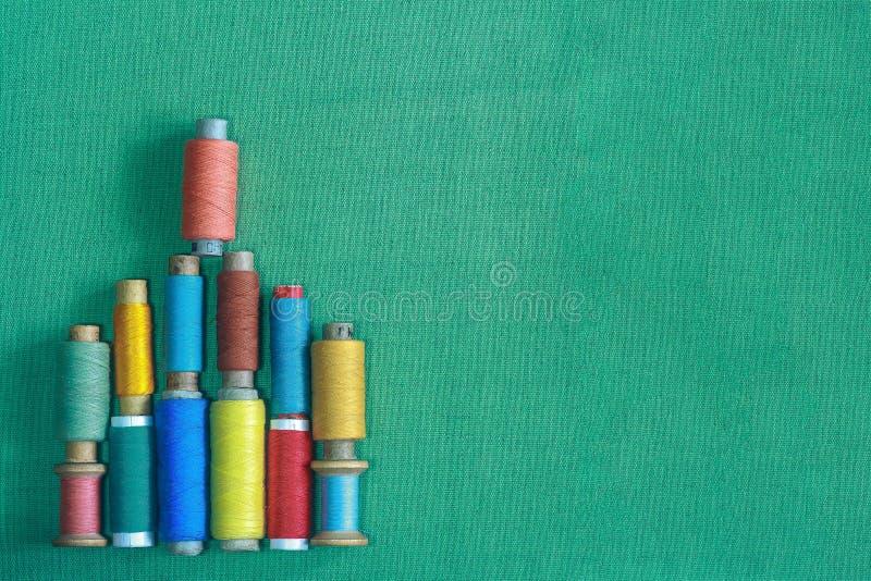 Rij van kleurrijke naalddraden, sleepboten, vaartuigen, naaiconcept Meerkleurige schroefdraad op een turkooisstof stock afbeelding