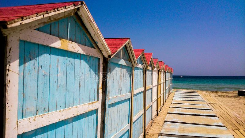 Rij van kleurrijke strandcabines dichtbij het overzees stock foto