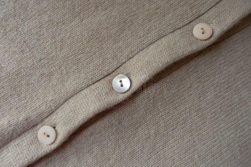 Rij van knopen op beige gebreide stof royalty-vrije stock foto