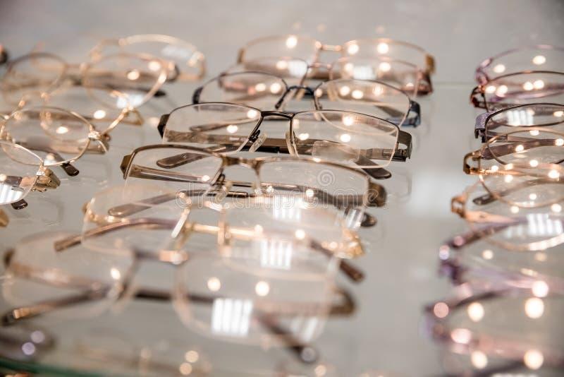 Rij van luxeoogglas bij een opticiensopslag oogglazen bij opticien Sideview van modieuze optische oogglazen, het hangen stock foto's
