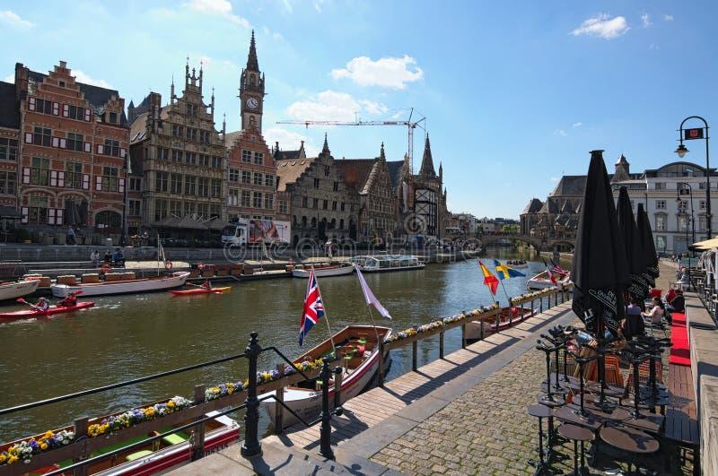 Rij van middeleeuwse gebouwen langs de toeristenboten die op Lys River het Nederlands drijven: Leie stock fotografie