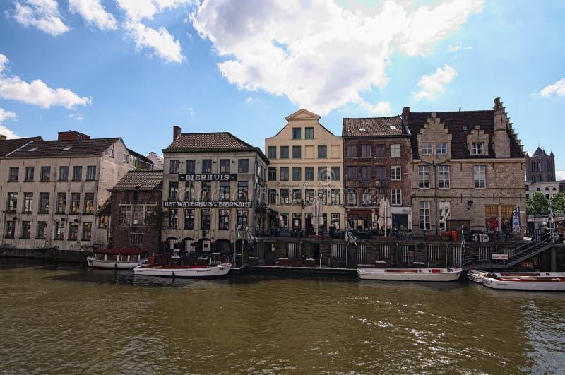 Rij van middeleeuwse gebouwen langs Lys River het Nederlands: Leie met toeristenboten dichtbij de bank stock fotografie