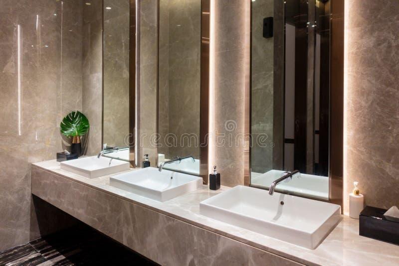 Rij van modern marmeren ceramisch wasbassin in openbaar toilet, toilet in restaurant of hotel of winkelcomplex, binnenhuisarchite stock afbeelding