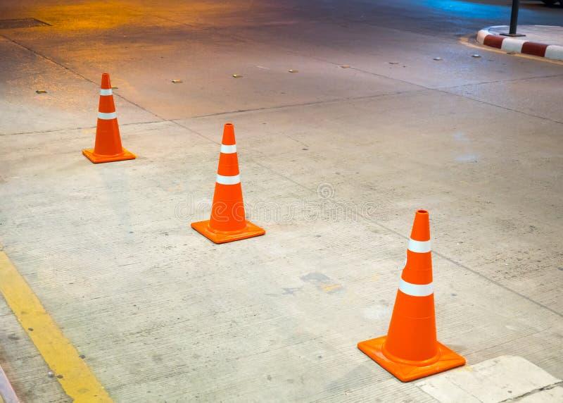 Rij van oranje verkeerskegels op betonweg royalty-vrije stock afbeelding