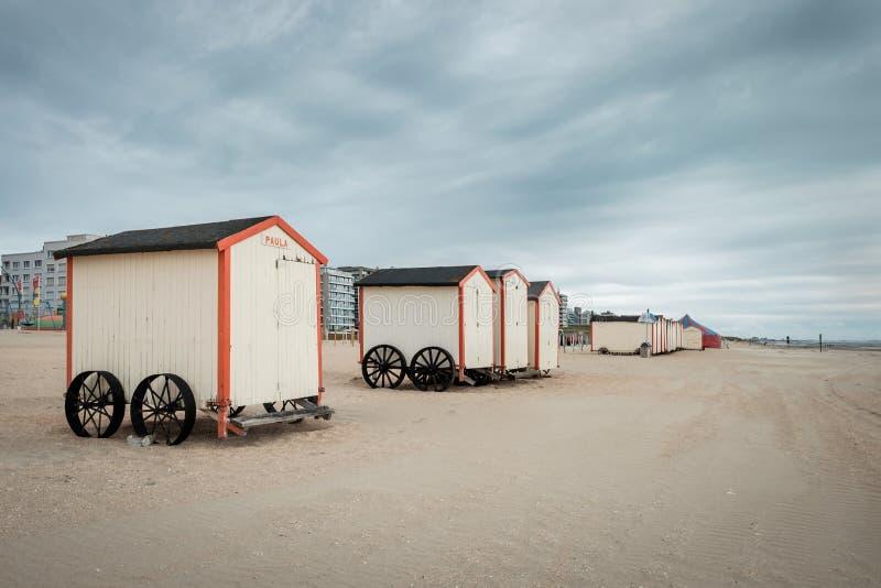 Rij van pastelkleur gekleurde strandhutten op een bewolkte dag stock afbeeldingen
