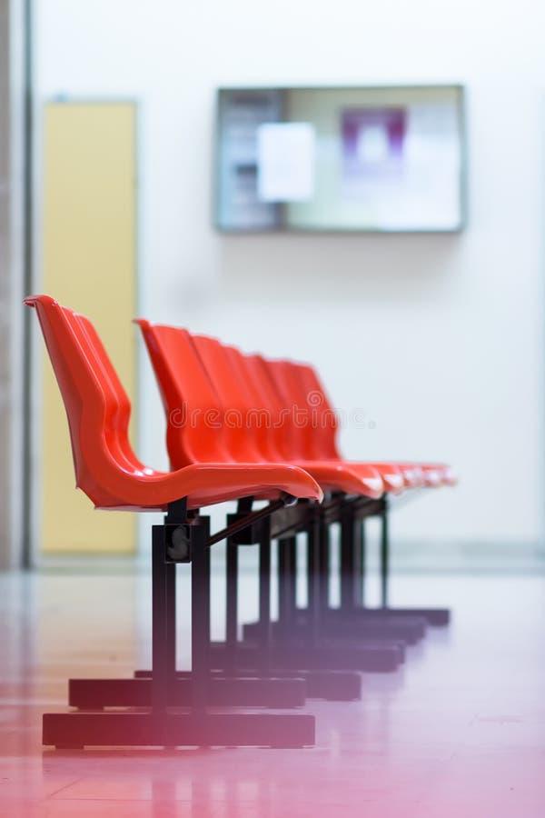 Rij van rode plastic stoelen in het ziekenhuis royalty-vrije stock afbeeldingen