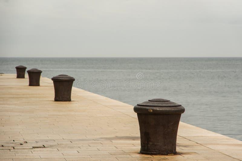Rij van roestige meerpalen tegen het Adriatische zeegezicht stock afbeeldingen