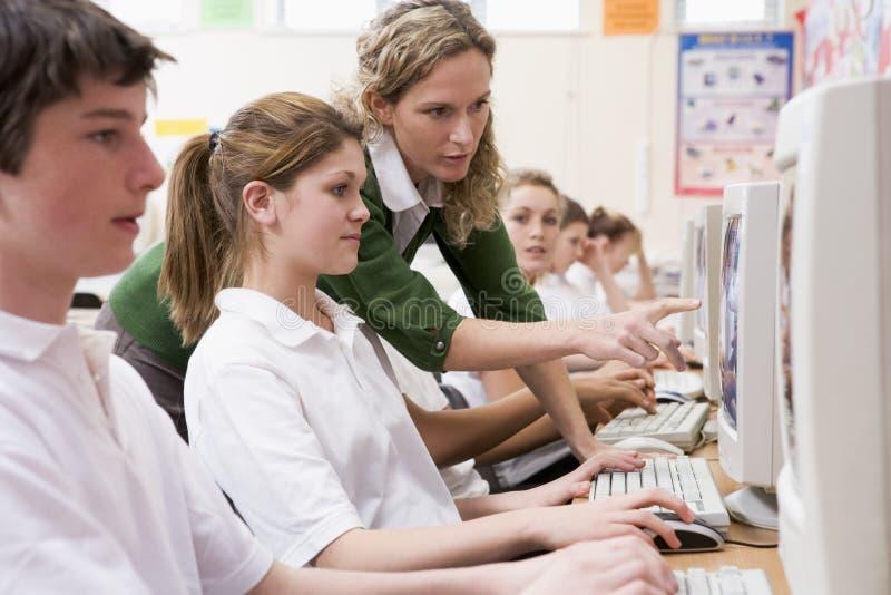 Rij van schoolkinderen die binnen op computers bestuderen royalty-vrije stock fotografie