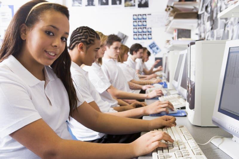 Rij van schoolkinderen die binnen op computers bestuderen stock foto's