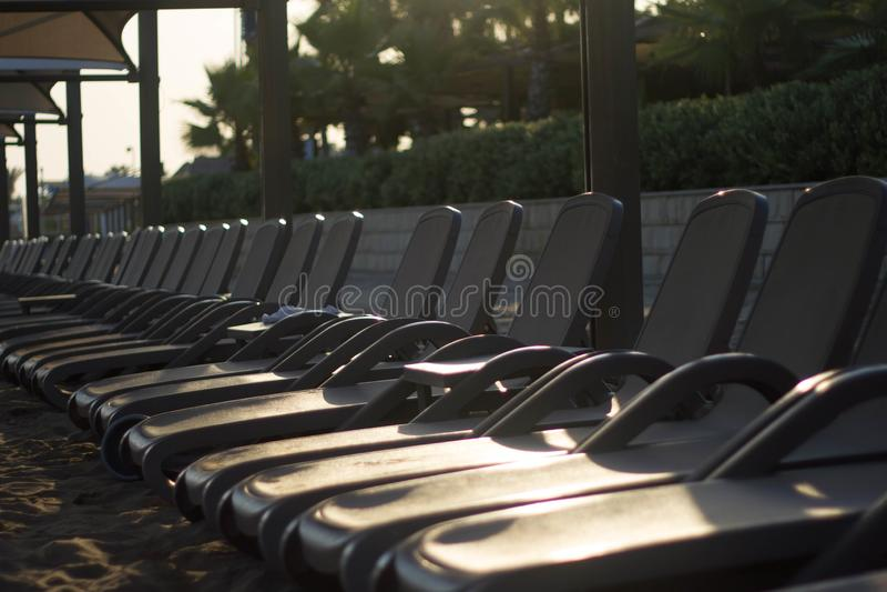 Rij van sunbeds met paraplu's op het strand door het overzees bij zonsondergang Grijze sunbeds zijn op het strand stock fotografie