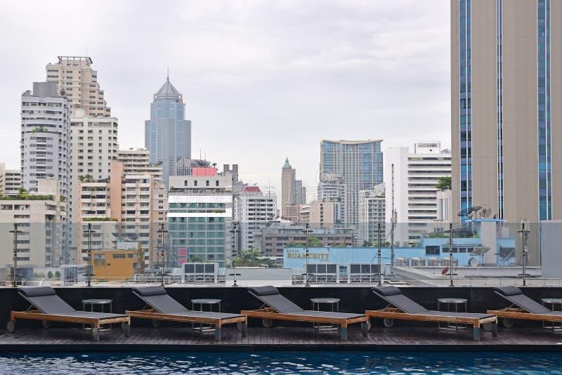Rij van Sundeck bij een het dakpool die van het luxehotel de stadscentrum overzien van Bangkok stock fotografie