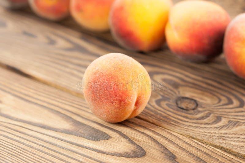Rij van verse gehele rijpe perziken en één perzik afzonderlijk stock fotografie