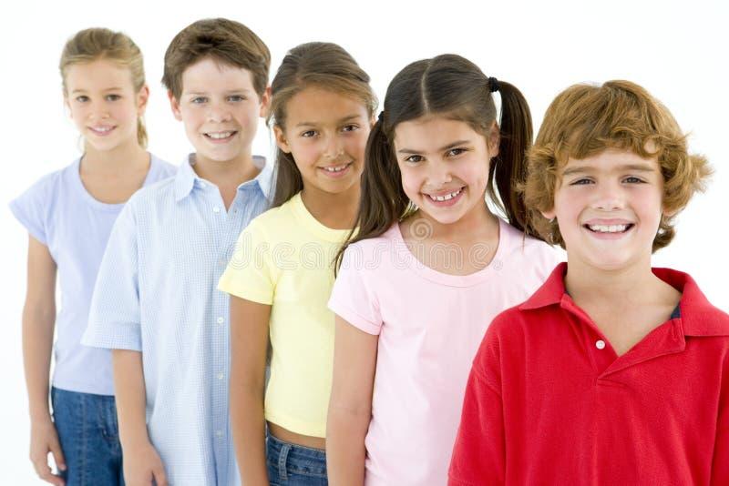 Rij van vijf het jonge vrienden glimlachen royalty-vrije stock fotografie