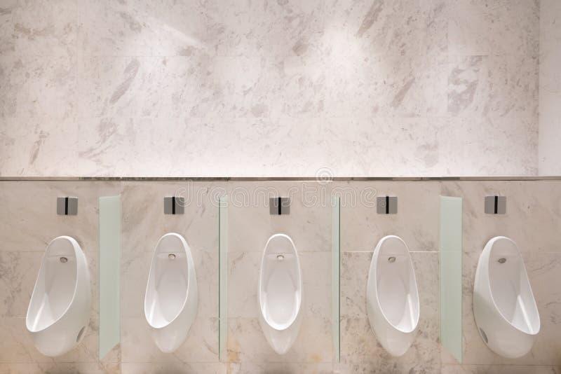 Rij van vijf urinoirs met infrarode sensor, op marmeren muur, in het openbare toilet van mensen stock foto's