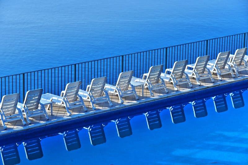 Rij van vrije sunbeds bij het zwembad in een toeristische toevlucht royalty-vrije stock afbeelding
