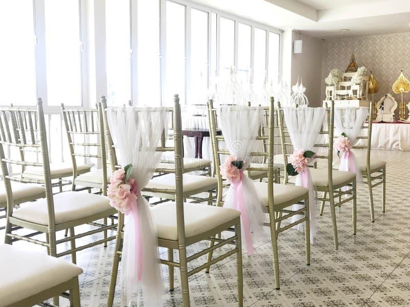 Rij van witte die stoelen met bloem in huwelijksceremonie worden verfraaid stock foto