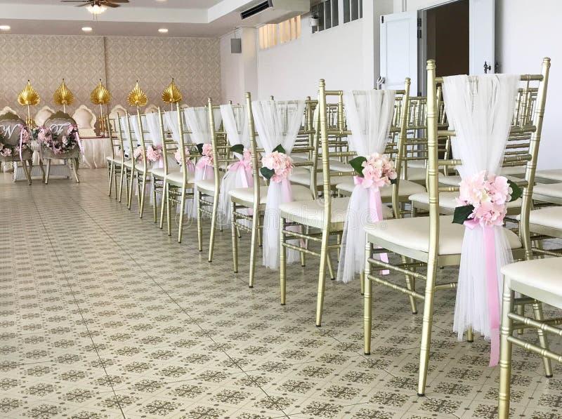 Rij van witte die stoelen met bloem in huwelijksceremonie worden verfraaid stock afbeelding