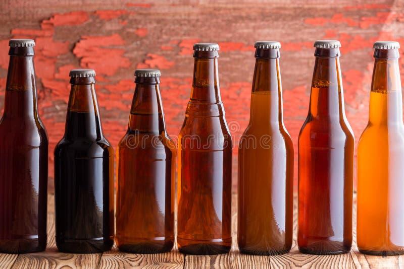 Rij van zeven types van bier in verschillende flessen stock afbeelding