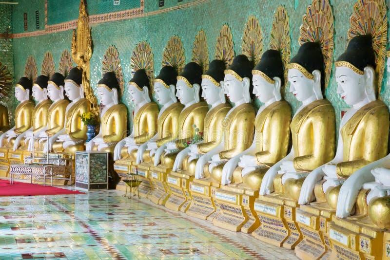 Rij van zitting Buddhas in tempel van Myanmar stock afbeelding