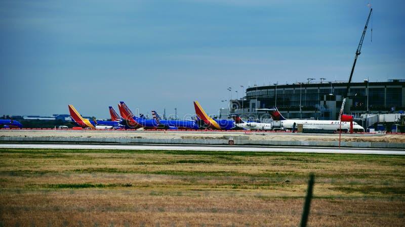 Rij van Zuidwesten en Delta Airlines-vliegtuigen bij hun poorten wordt geparkeerd die stock fotografie