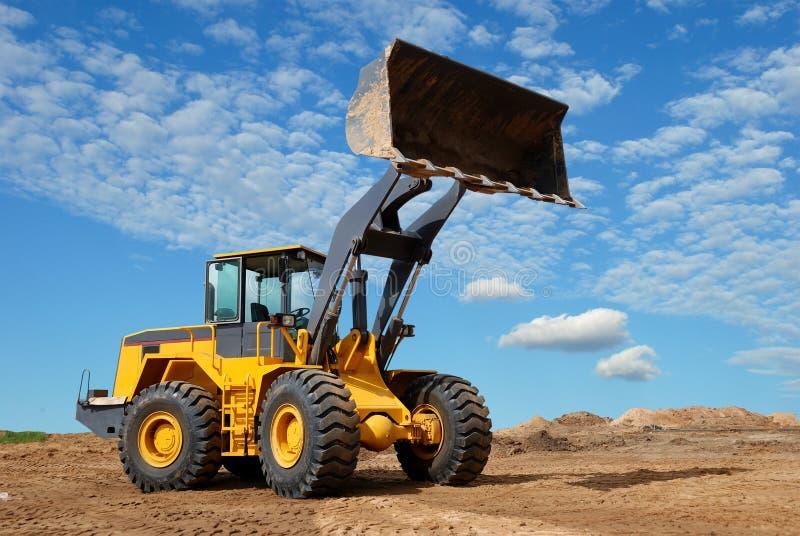 Rijd laderbulldozer in sandpit stock foto's