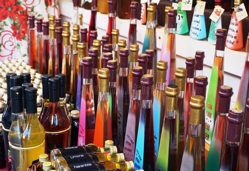 Rijeka, Croácia, o 29 de dezembro de 2018 Garrafas de vidro coloridos com o licor alcoólico exposto para a venda no suporte imagem de stock