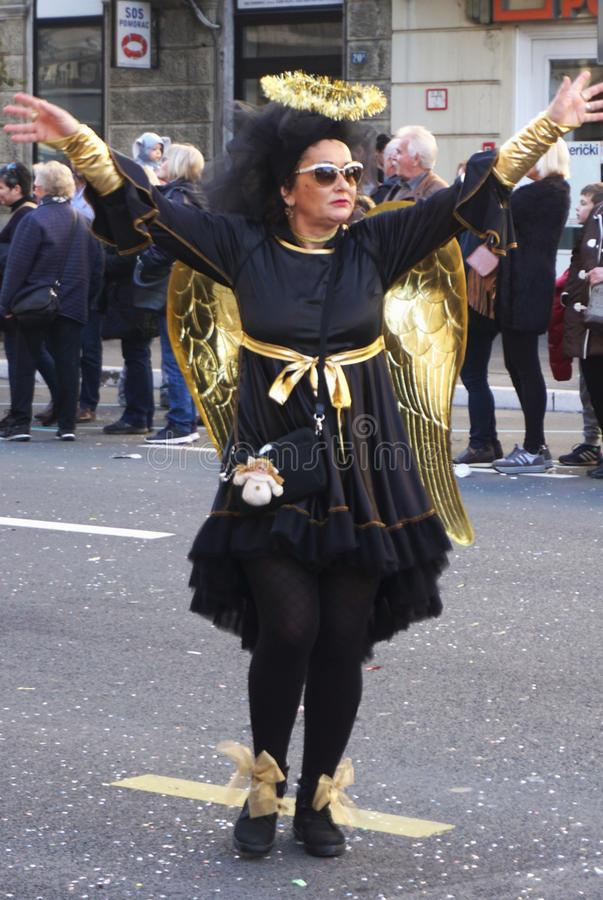 Rijeka, Croatia, March 3rd, 2019. Woman in black angel with golden wings costume on carnival. Rijeka, Croatia, March 3rd, 2019. Woman in black angel with golden royalty free stock images