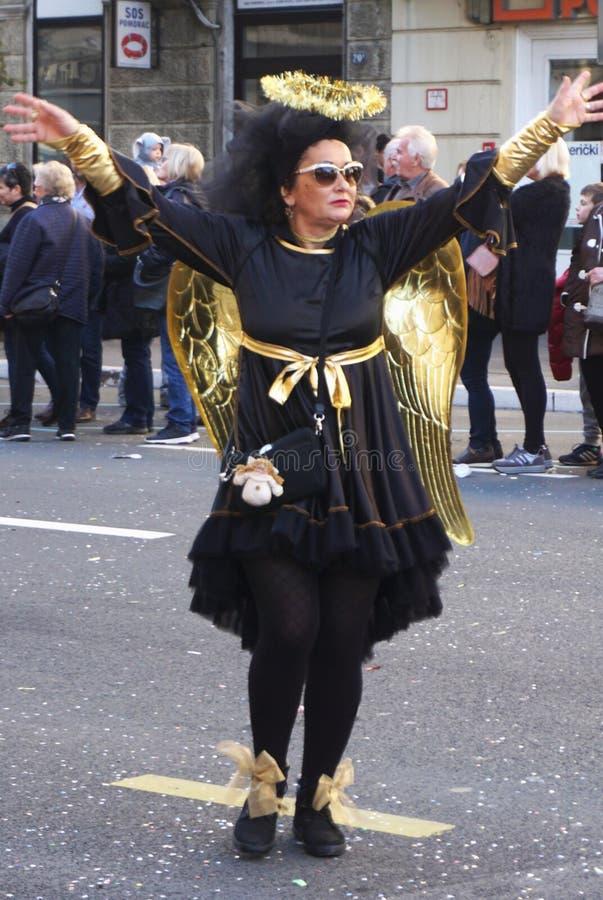 Rijeka Kroatien, mars 3rd, 2019 Kvinna i svart ängel med den guld- vingdräkten på karneval royaltyfria bilder