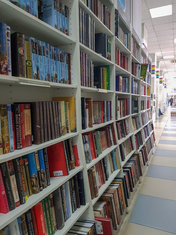 Rijen die van verschillende kleurrijke boeken op de planken in de moderne boekhandel liggen stock foto