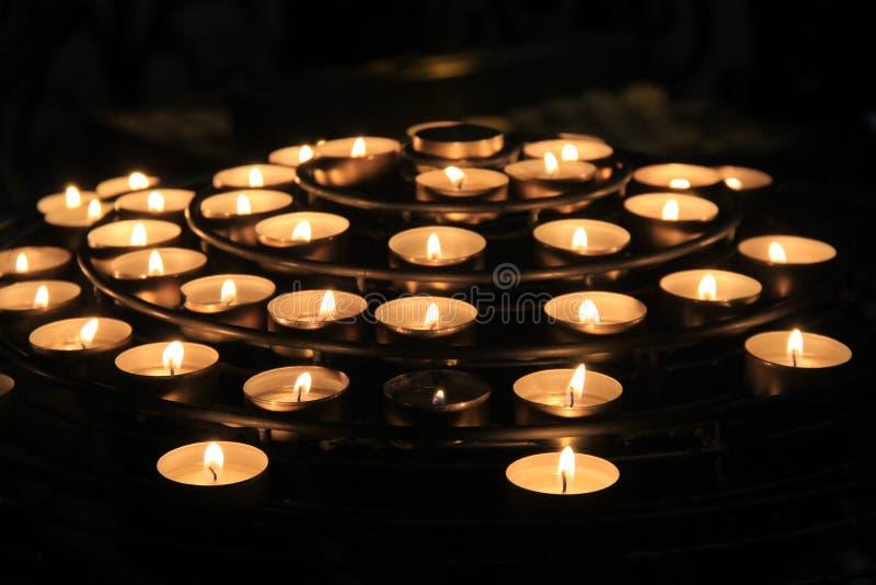 Rijen van aangestoken kaarsen, gietende zachte schaduwen in ruimte van gebed stock foto