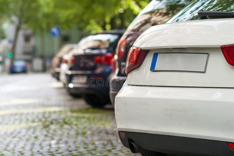 Rijen van auto's op de kant van de weg in woondistrict worden geparkeerd dat stock fotografie