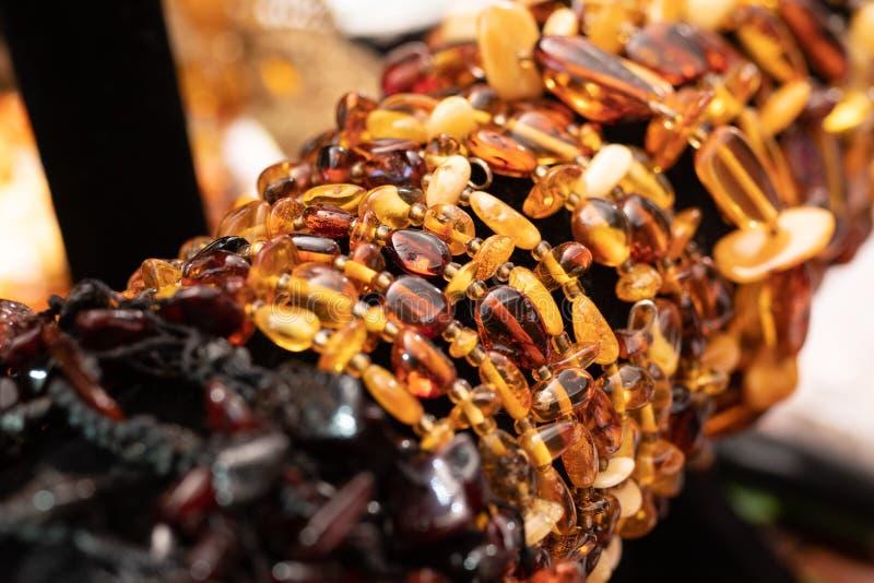 Rijen van Baltische amberhalsbanden en armbanden stock afbeeldingen