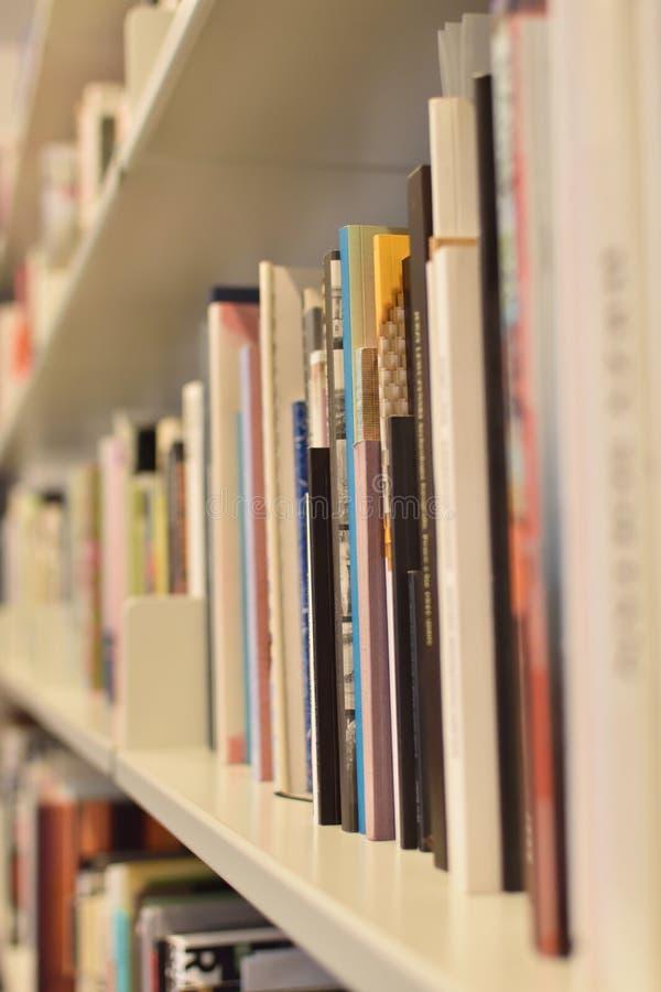Rijen van boeken op witte boekenrekken royalty-vrije stock afbeelding