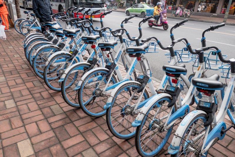 Rijen van fiets voor huur op voetpad om luchtvervuiling te verminderen stock afbeelding