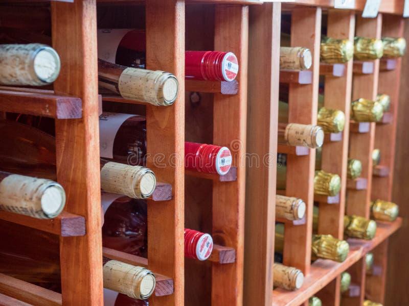 Rijen van flessen rode en witte wijnen op houten wijnrek stock fotografie