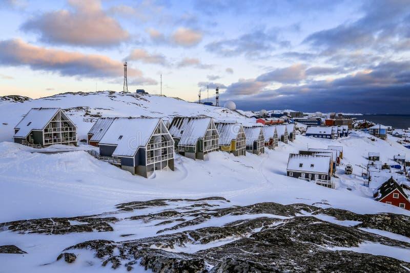 Rijen van kleurrijke Inuit-huizen die in de sneeuw en de rotsen verbergen met stock foto