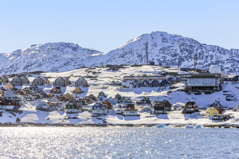 Rijen van kleurrijke Inuit-huizen langs de fjord met sneeuwberg stock afbeeldingen