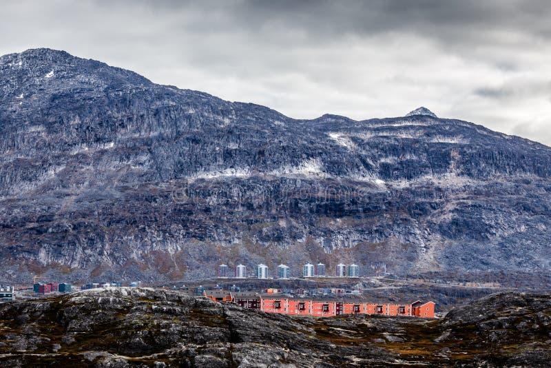 Rijen van kleurrijke moderne Inuit-huizen onder bemoste stenen met gre stock afbeelding